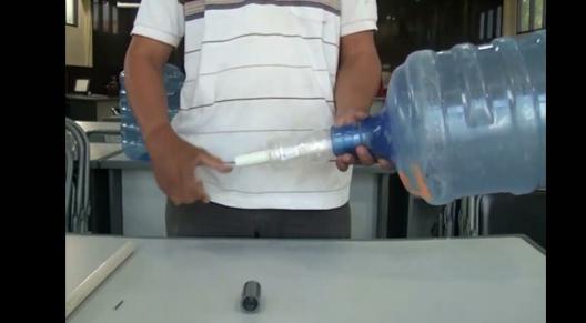 Memasukkan pipa paralon ke dalam galon